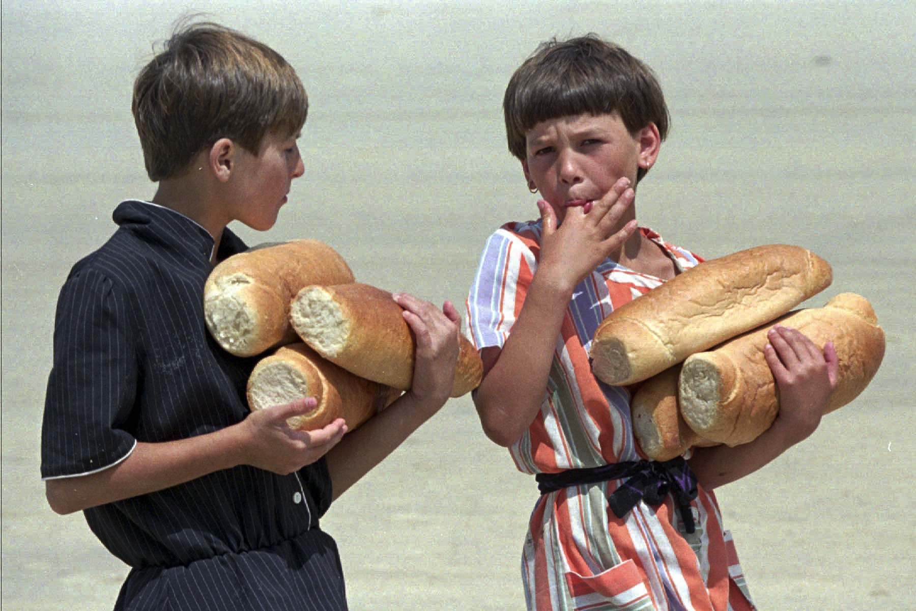 FILE- In this July 19, 1995, file picture, Bosnian refugee children from Srebrenica, carry loaves of bread, which they received from the United Nations at the refugee camp at Tuzla airport.  Survivors of the genocide in the eastern Bosnian town of Srebrenica, mainly women, will on Saturday July 11, 2020, commemorate the 25th anniversary of the slaughter of their fathers and brothers, husbands and sons. The slaughter was the only atrocity of the brutal war that has been confirmed an act of genocide. (AP Photo/Michel Euler, File)
