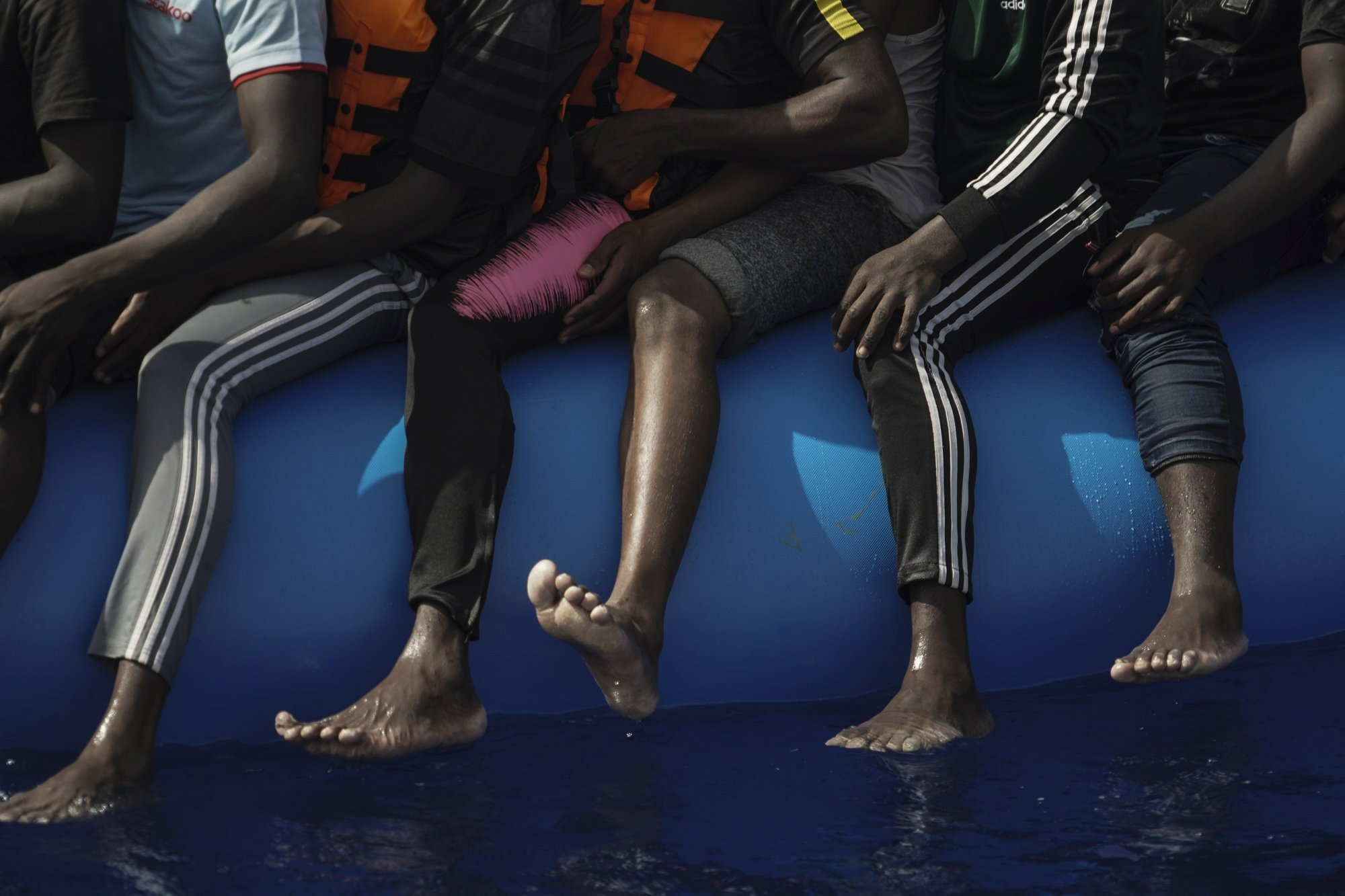 In this Sept. 17, 2019 photo, migrants sit on an overcrowded rubber boat as they wait to be rescued by the Ocean Viking humanitarian ship run by SOS Mediterranée and Doctors Without Borders in the Mediterranean Sea north of Libya. The EU has sent more than 327.9 million euros to Libya, with an additional 41 million approved in early December, largely funneled through UN agencies. However, the AP found that in a country without a functioning government, huge sums of European money have been diverted - in some cases with the knowledge of UN officials - to intertwined networks of militiamen, traffickers and coast guard members who exploit migrants. (AP Photo/Renata Brito)