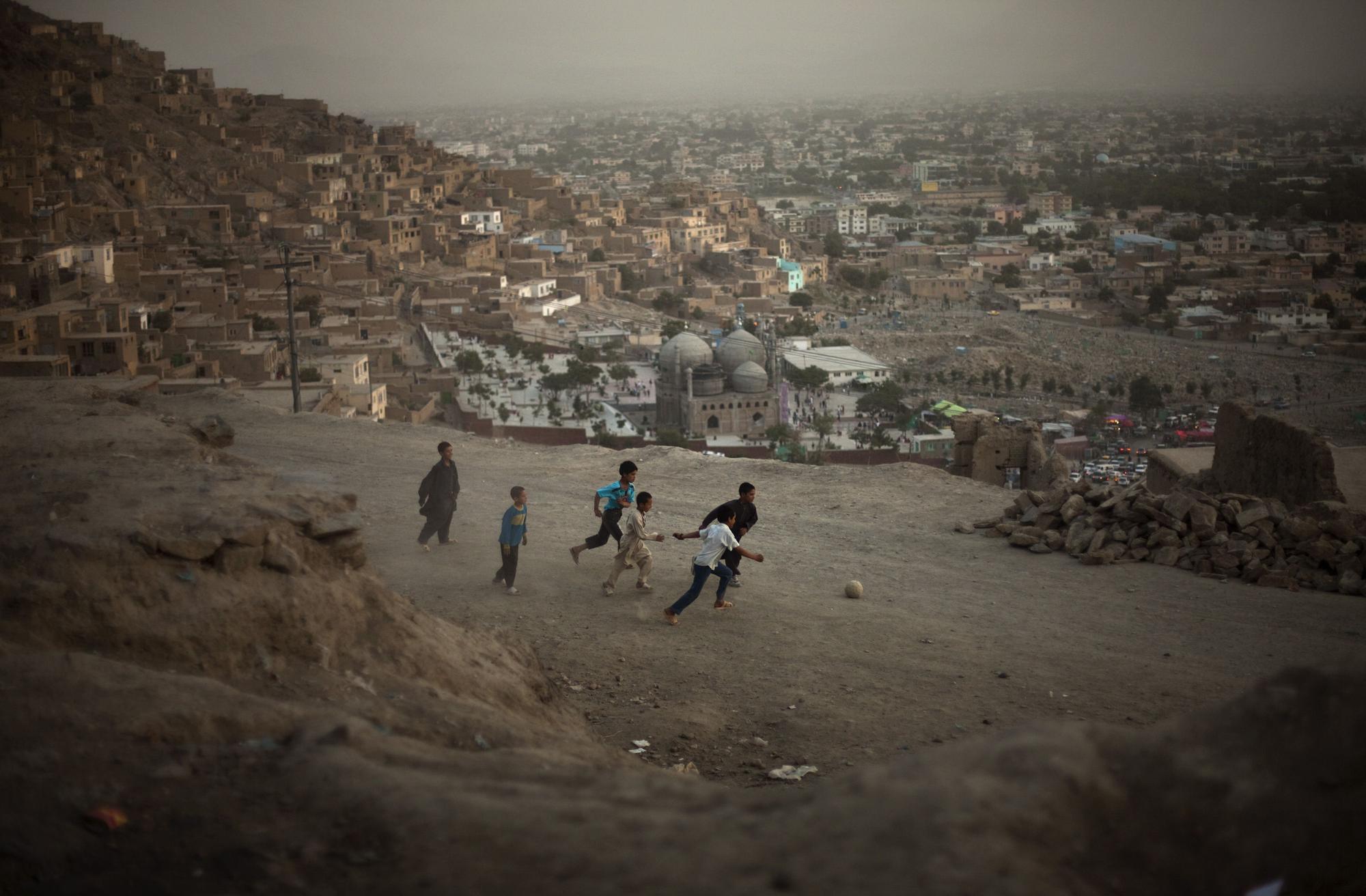 Afghan children play football in a street in Kabul, Afghanistan on Friday, July 17, 2009. (AP Photo/Emilio Morenatti)