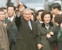 FILE - In this Dec. 22, 1997, file photo former South Korean President Roh Tae-woo, with his wife Kim Ok-sook standing beside him, waves to his supporters and neighbors upon arrival at his home after he was released from the Seoul prison in a special amnesty. Seoul hospital says Tuesday, Oct. 26, 2021, former South Korean President Roh has died (Yonhap via AP, Fiie)