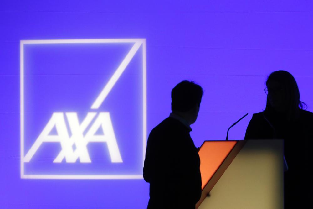 FILE - In this Feb. 21, 2019, file photo, people stand in front of the logo of AXA Group prior to the company's 2018 annual results presentation, in Paris. The cyber insurance industry, once a profitable niche, is now in the crosshairs of ransomware criminals. Pressure is building on the industry to stop reimbursing for ransoms, but so far only one major cyber insurer, AXA, is doing so — and only with new policies in France. To try to absorb the growing onslaught and stay profitable, insurers are retooling coverage, demanding clients up their security.  (AP Photo/Thibault Camus, File)