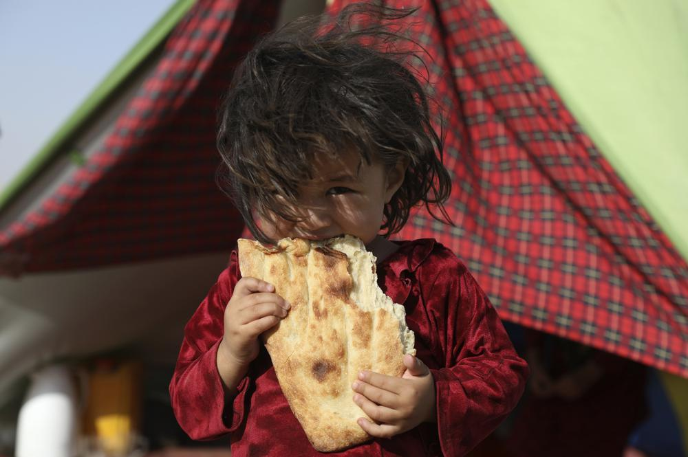 An internally displaced Afghan girl whose family fled their home due to fighting between the Taliban and Afghan security personnel, eats bread as she stand in front of her makeshift tent at a camp on the outskirts of Mazar-e-Sharif, northern Afghanistan, Thursday, July 8, 2021. As the Taliban surge through the north of Afghanistan, a traditional stronghold of US-allied warlords and an area dominated by the country's ethnic minorities, thousands of families like this girl's are fleeing their homes, fearful of living under the insurgents ' rule.  (AP Photo/Rahmat Gul)