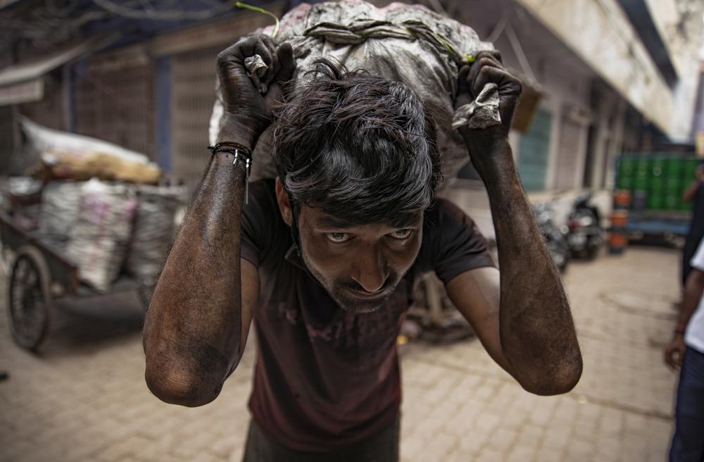 A laborer carries a load on his back at the old market in Prayagraj, Uttar Pradesh, India, Thursday, July 8, 2021. (AP Photo/Rajesh Kumar Singh)