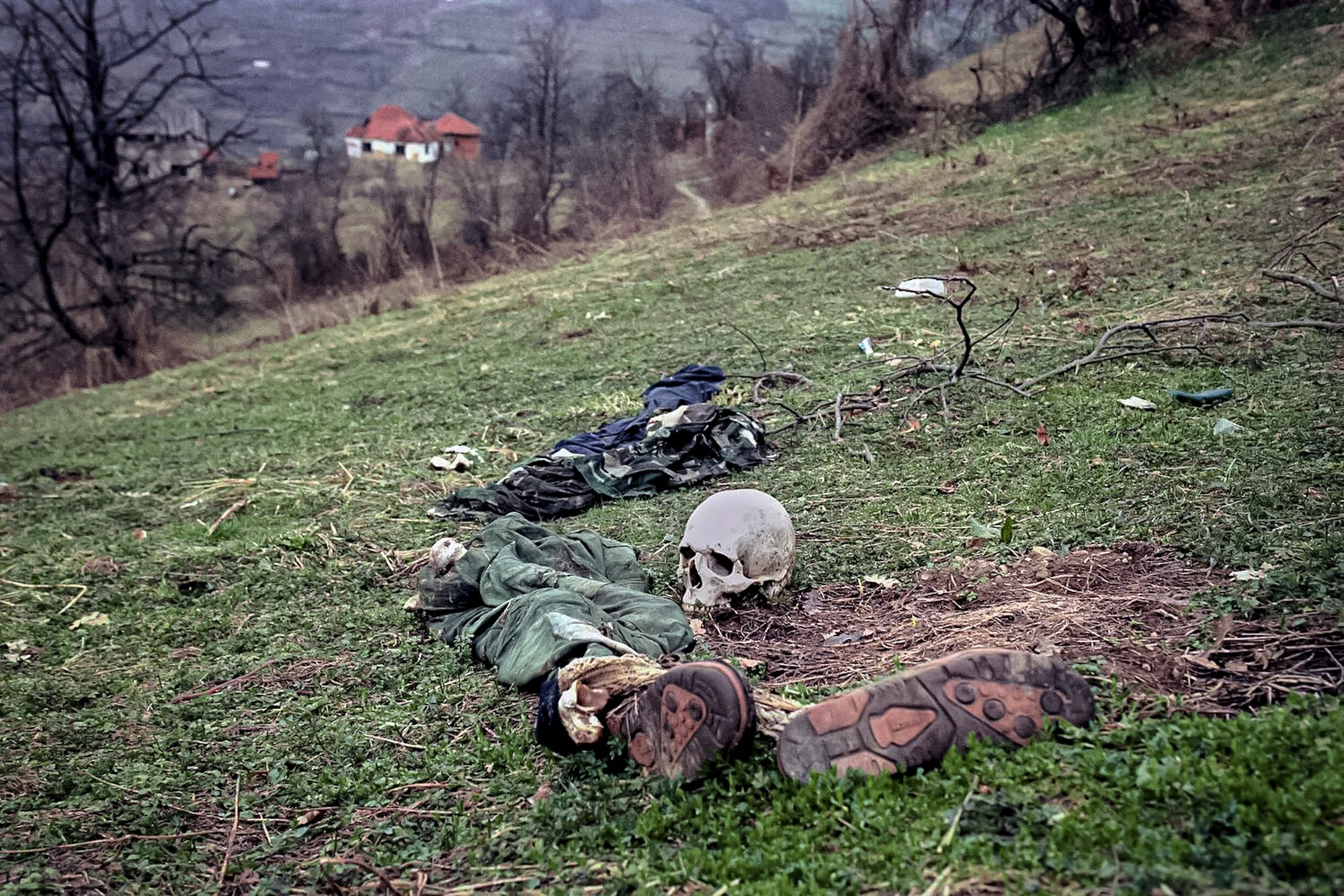 FILE- In this Tuesday, April 2, 1996, file photo, the remains of two bodies and pieces of clothing lie in a field at a suspected mass grave site in the village of Konjevic Polje, approximately 20km (12 miles), north west of Srebrenica.  Survivors of the genocide in the eastern Bosnian town of Srebrenica, mainly women, will on Saturday July 11, 2020, commemorate the 25th anniversary of the slaughter of their fathers and brothers, husbands and sons.  At least 8,000 mostly Muslim men and boys were chased through woods in and around Srebrenica by Serb troops in what is considered the worst carnage of civilians in Europe since World War II. The slaughter was also the only atrocity of the brutal war that has been confirmed an act of genocide.(AP Photo/Vadim Ghirda, File)