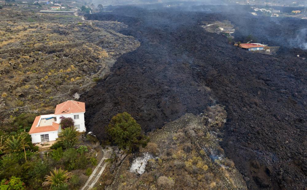 La lava de una erupción volcánica fluye destruyendo casas en la isla de La Palma en Canarias, España, martes 21 de septiembre de 2021. Un volcán inactivo en una pequeña isla española en el Océano Atlántico entró en erupción el domingo, lo que obligó a la evacuación de miles de personas. gente.  Enormes columnas de humo blanco y negro se dispararon desde una cresta volcánica donde los científicos habían estado monitoreando la acumulación de lava fundida debajo de la superficie.  (Foto AP / Emilio Morenatti)