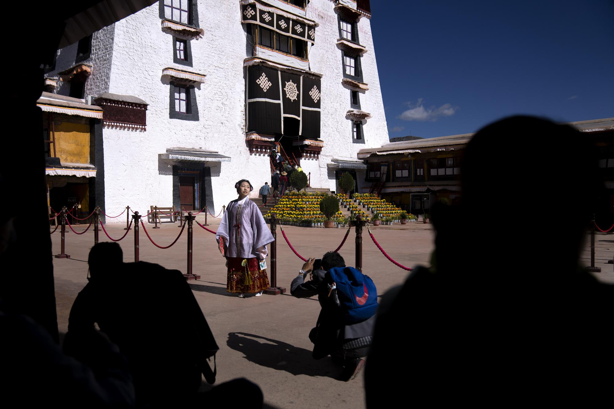 A Chinese tourist in Tibetan dress poses for a photo in a courtyard at the Potala Palace in Lhasa in western China's Tibet Autonomous Region, Tuesday, June 1, 2021. Tourism is booming in Tibet as more Chinese travel in-country because of the coronavirus pandemic, posing risks to the region's fragile environment and historic sites. (AP Photo/Mark Schiefelbein)