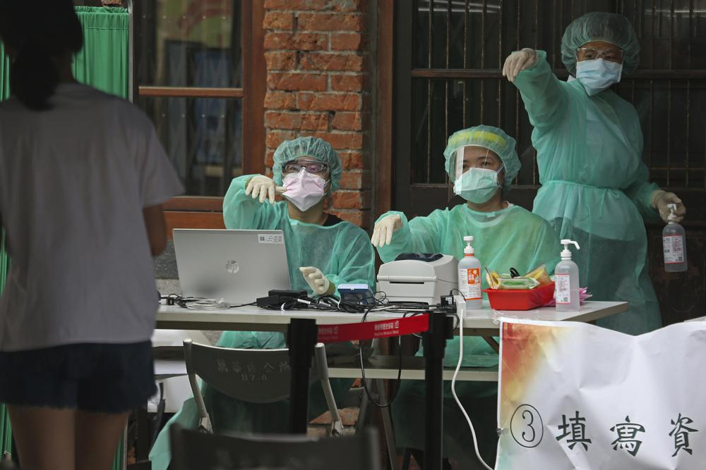 FILE - In this May 18, 2021, file photo, medical personnel wearing protective gear, guide people at a rapid coronavirus testing center after the infection alert rose to level 3 in Taipei, Taiwan. After a year of success, Taiwan is struggling with its largest outbreak since the pandemic began. When locally transmitted cases started being found in May 2021, it soon became clear that the central government was ill prepared not only to contain them, but to even detect them on a large scale due to a lack of investment in and a bias against rapid testing. (AP Photo/Chiang Ying-ying, File)