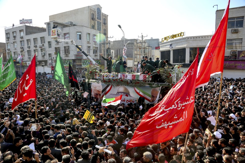 In this photo provided by The Iranian Students News Agency, ISNA, flag draped coffins of Gen. Qassem Soleimani and his comrades who were killed in Iraq in a U.S. drone strike, carried on a truck surrounded by mourners during their funeral in southwestern city of Ahvaz, Iran, Sunday, Jan. 5, 2020. (Alireza Mohammadi/ISNA via AP)