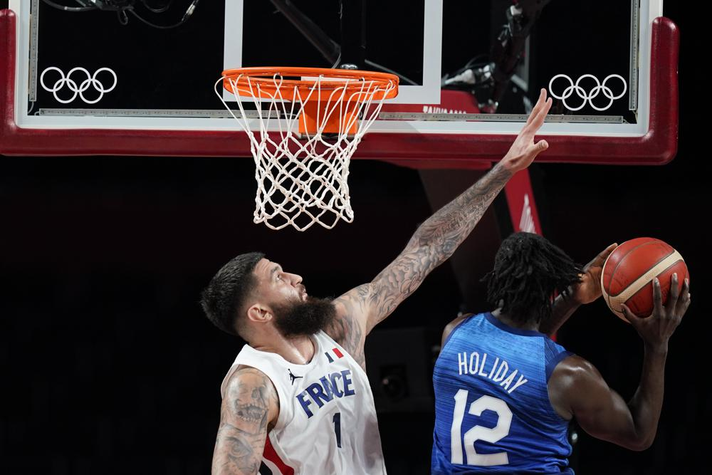 France's Vincent Poirier tries to block a shot by United States' Jrue Holiday (12) during a men's basketball preliminary round game at the 2020 Summer Olympics, Sunday, July 25, 2021, in Saitama, Japan. (AP Photo/Charlie Neibergall)