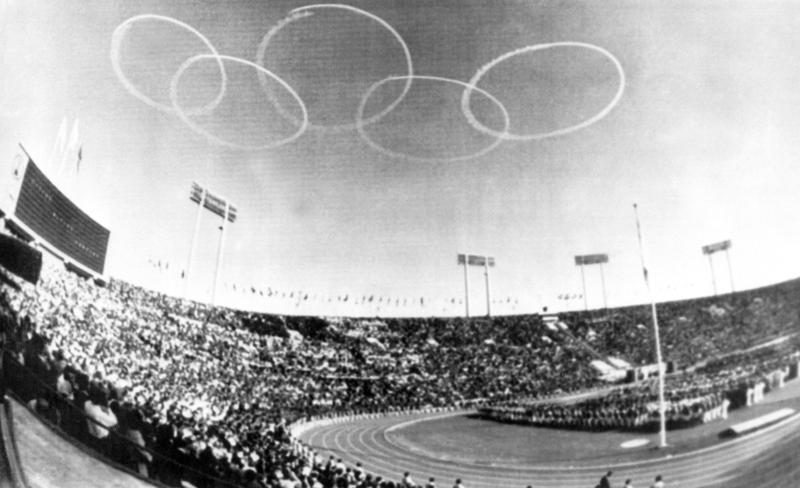 FILE - In this Oct. 10, 1964, file photo, vapor trails from Japanese Self-Defense Force jets form the Olympic emblem of the five rings above the National Stadium in Tokyo for the official opening of the XVIII Olympiad, first even held in Asia. Every Japanese of a certain age has memories of the 1964 Tokyo Olympics. Even younger Japanese have connections through parents or aunts and uncles who saved old photos, faded certificates, or recall getting a television for the first time to watch the Games. (AP Photo, File)
