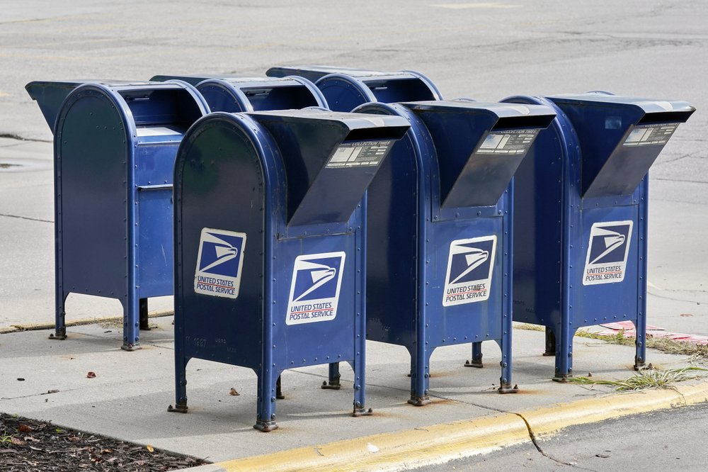 Facing public pressure and lawsuits, Postmaster General Louis DeJoy says he is suspending several of his initiatives to mail delivery
