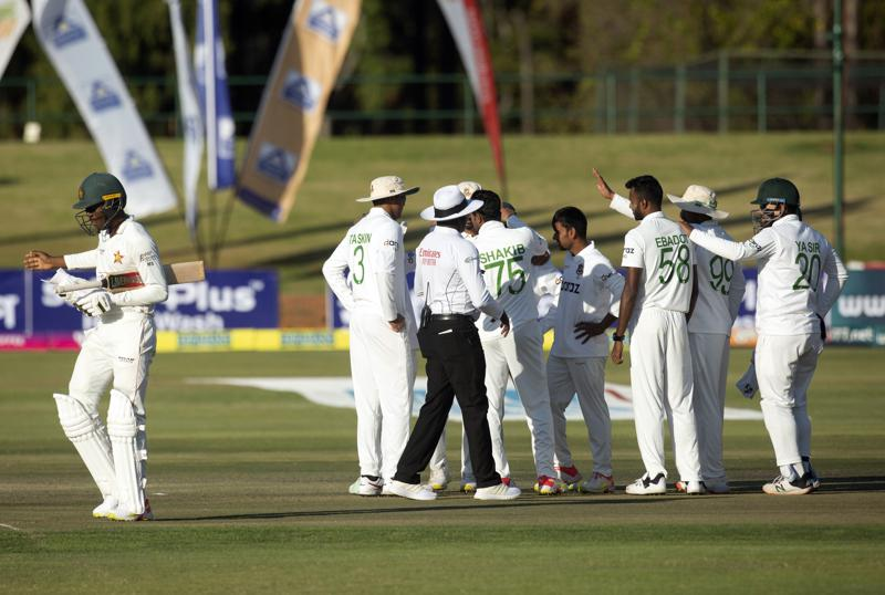 Zimbabwe batsman Milton Shumba,left, walks off the pitch after been dismissed on the second day of the test cricket match between Zimbabwe and Bangladesh at Harare Sports Club in Harare,Thursday, July,8, 2021.(AP Photo/Tsvangirayi Mukwazhi)