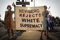 Cherice Boch, left, and her son Espen take part in a protest on Aug. 24 2021, in Newberg, Ore., against a new school policy that bans Black Lives Matter and Pride flags across Newberg School District facilities. The policy has prompted a torrent of recriminations and threats to boycott the town and its businesses. (Jozie Donaghey/The Oregonian via AP)