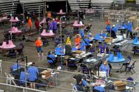FILE - In this May 6, 2021, file photo, Maricopa County ballots cast in the 2020 general election are examined and recounted by contractors working for Florida-based company, Cyber Ninjas at Veterans Memorial Coliseum in Phoenix. Cyber Ninjas, the inexperienced contractor hired to run a partisan review of the 2020 election on behalf of Republicans in the Arizona Senate, is scheduled to present its findings to top GOP lawmakers on Friday, Sept. 24, 2021. Election experts say the review, funded almost entirely by supporters of former President Donald Trump who have promoted false claims of fraud, was beset by problems and incompetence. (AP Photo/Matt York, Pool, File)