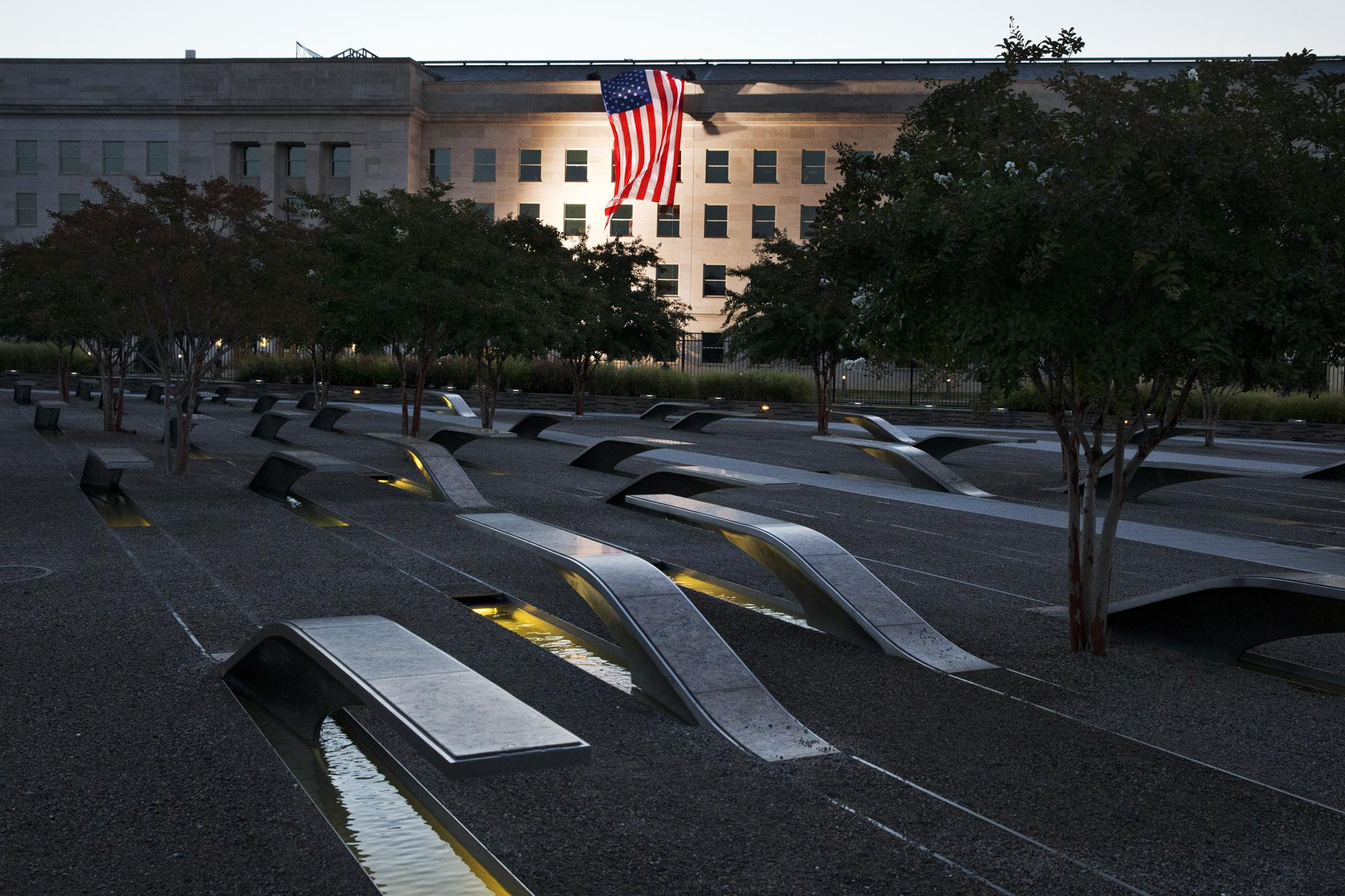 ADVANCE FOR PUBLICATION ON SUNDAY, SEPT. 5, AND THEREAFTER - FILE - In this Friday Sept. 11, 2015 file photo, a U.S. flag is draped on the side of the Pentagon where the attack took place 14 years earlier, seen from the Pentagon Memorial. (AP Photo/Jacquelyn Martin, File)