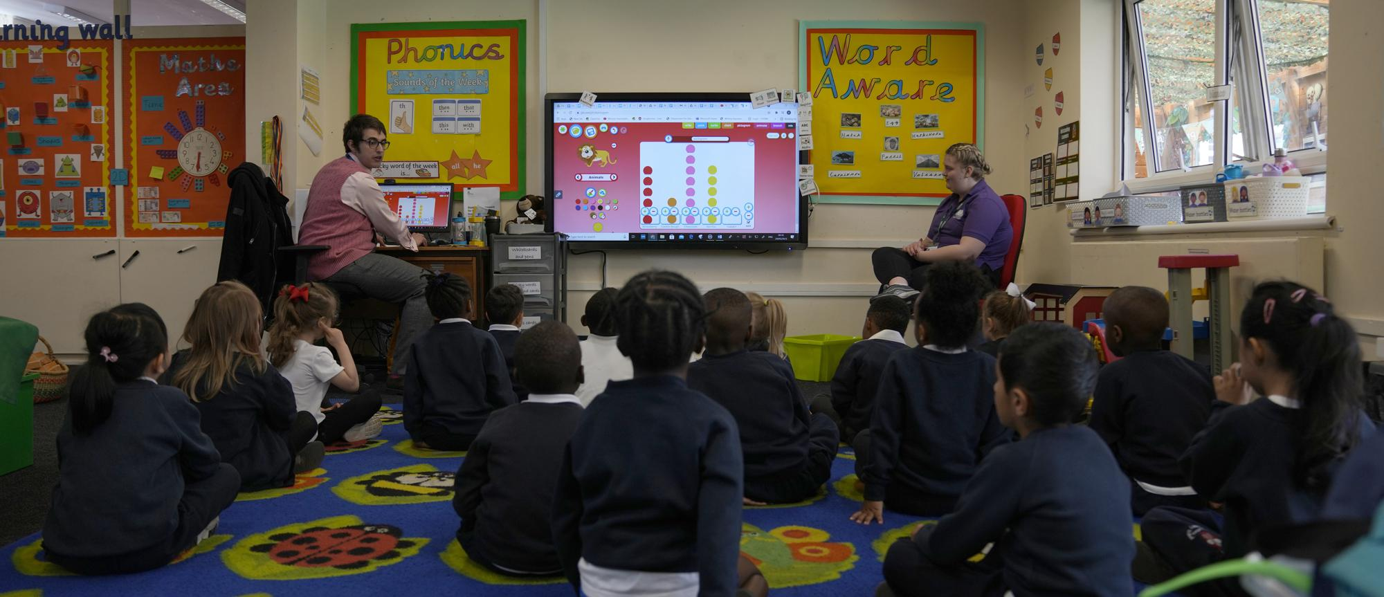 Alex Dickerson the reception class teacher, left leads the class at the Holy Family Catholic Primary School in Greenwich, London, Monday, May 24, 2021. Holy Family, like schools across Britain, is racing to offset the disruption caused by COVID-19, which has hit kids from low-income and ethnic minority families hardest.(AP Photo/Alastair Grant)