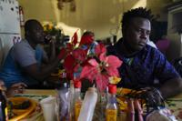 Robins Exile, of Haiti, eats at a Haitian restaurant, Monday, Sept. 20, 2021, in Tijuana, Mexico. Exile arrived to Tijuana the day before after changing his plans to head to the Texas border where thousands of Haitians have converged in recent days and now face deportation. He said messages on WhatsApp and Facebook from fellow Haitian migrants and their videos on YouTube warned him to steer clear of Ciudad Acuna, Mexico, across from Del Rio, Texas, and said it no longer is the easy place to cross into the U.S. that it was just a few weeks ago. (AP Photo/Gregory Bull)