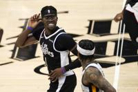 Los Angeles Clippers guard Reggie Jackson, left, smiles as Utah Jazz guard Jordan Clarkson after scoring during the second half of Game 3 of a second-round NBA basketball playoff series Saturday, June 12, 2021, in Los Angeles. (AP Photo/Mark J. Terrill)