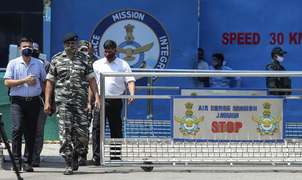 Indian paramilitary officials come out of the Jammu air force station after two suspected blasts were reported early morning in Jammu, India, Sunday, June 27, 2021. Indian officials said Sunday they suspected explosives-laden drones were used to attack the air base in the disputed region of Kashmir, calling it the first such incident of its kind in India.