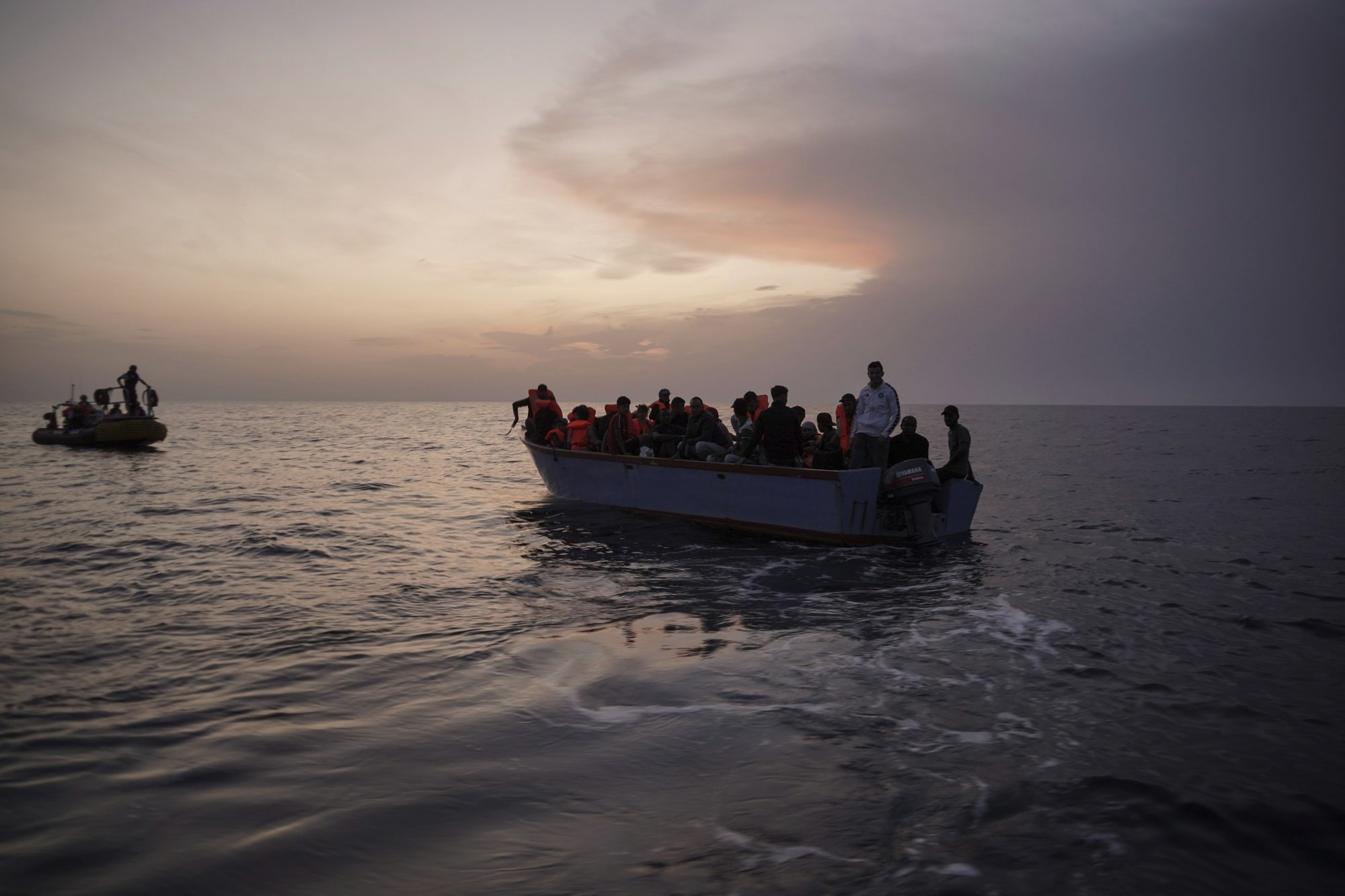 In this Sept. 19, 2019 photo, migrants on an overcrowded wooden boat wait to be rescued by the Ocean Viking humanitarian ship in the Mediterranean Sea. The misery of migrants in Libya has spawned a thriving and highly lucrative business, in part funded by the EU and enabled by the United Nations, an Associated Press investigation has found. (AP Photo/Renata Brito)