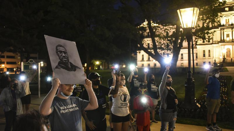 Mitchell Eithun of Lansing, Mich., holds up a sketch of George Floyd created by friend Cheryl Gamber, while others hold up lit cell phones to remember Floyd on Tuesday evening, May 25, 2021, during a memorial at the state Capitol in Lansing, Mich., a year after Floyd's death at the hands of Minneapolis police. The event was sponsored by Black Lives Matter Lansing. (Matthew Dae Smith/Lansing State Journal via AP)
