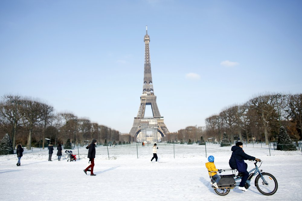 Workers use blowtorch to melt the ice at Eiffel Tower as snow blankets Europe