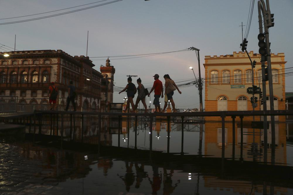 People walk on a wooden footbridge set up over a street flooded by the Negro River, in downtown Manaus, Amazonas state, Brazil, Tuesday, June 1, 2021. Rivers around Brazil's biggest city in the Amazon rain forest have swelled to levels unseen in over a century of record-keeping, according to data published Tuesday by Manaus' port authorities. (AP Photo/Edmar Barros)