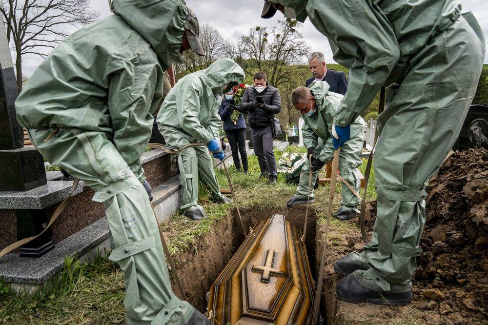 На этой фотографии, сделанной в субботу, 2 мая 2020 года, похоронные работники в армейских защитных костюмах опускают гроб 71-летнего Семена Мучки, который умер от коронавирусной болезни, в могилу на кладбище в Кринице, Украина. (AP Photo / Евгений Малолетка)