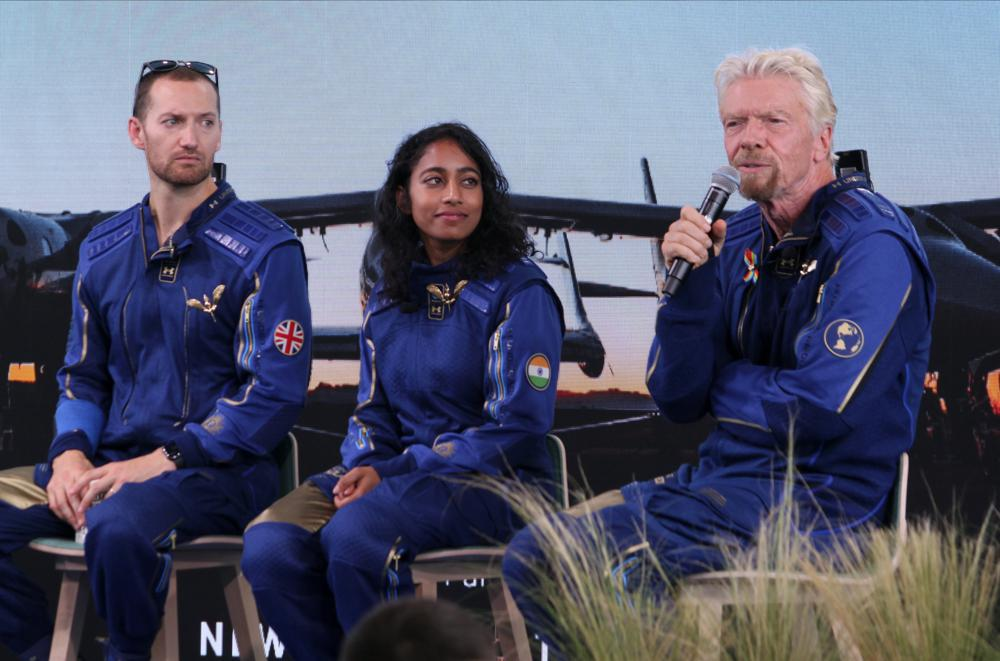 Richard Branson, right, answers questions while crewmates Sirisha Bandla and Colin Bennett listen during a news conference at Spaceport America near Truth or Consequences, N.M., on Sunday, July 11, 2021. Branson and the crew from his Virgin Galactic space tourism company reached an altitude of about 53 miles (88 kilometers) over the New Mexico desert before safely gliding back home to a runway landing at Spaceport America. (AP Photo/Susan Montoya Bryan)