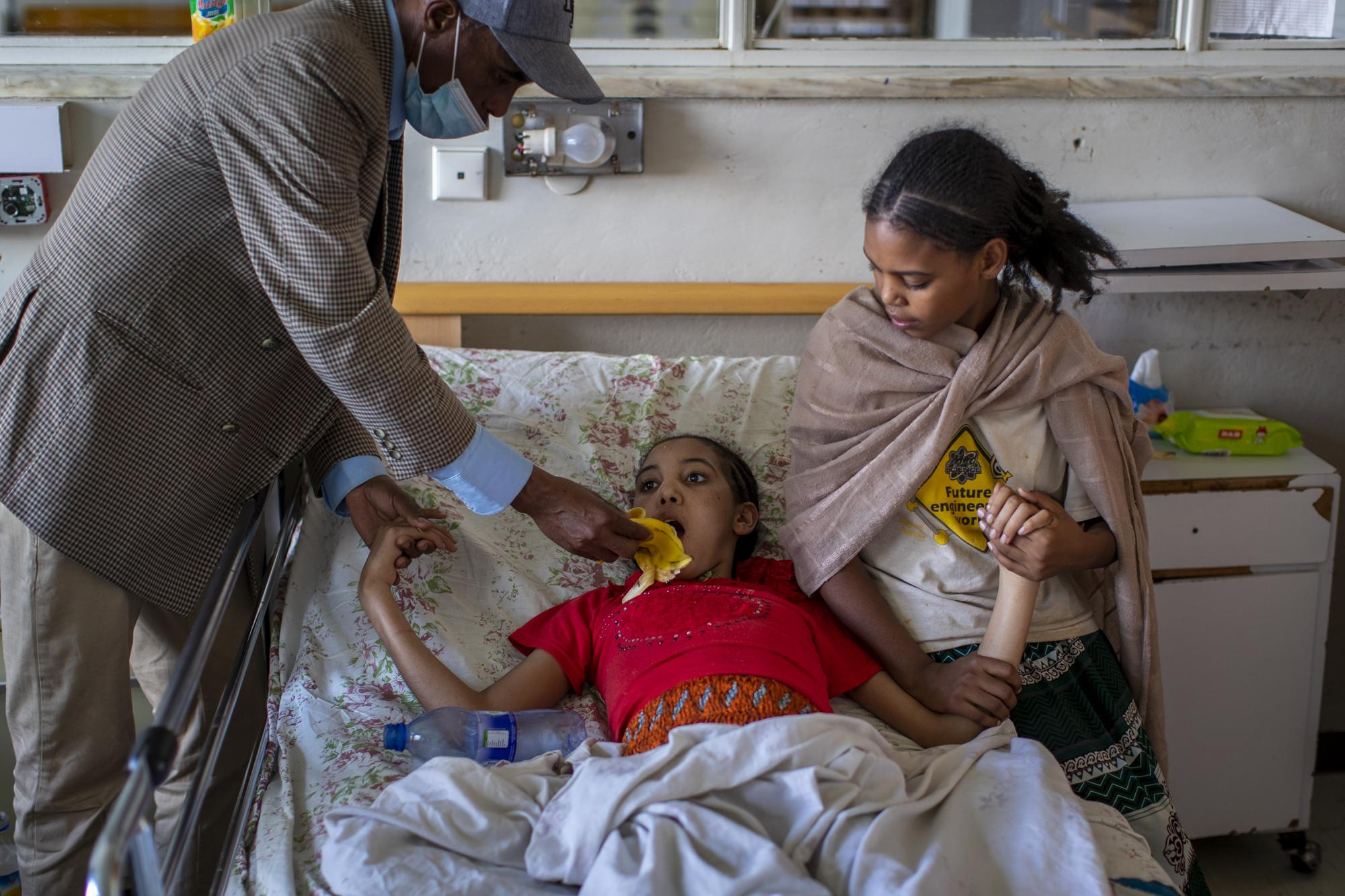 Akhberet Tadesa, 15, who is unable to feed herself and hasn't spoken or walked unaided since a shell exploding near her home left her in an apparent state of mental shock, is aided by her father Tadese Gebremedhin, left, and sister Fana, 13, right, at the Ayder Referral Hospital in Mekele, in the Tigray region of northern Ethiopia, on Thursday, May 6, 2021. As the Tigray People's Liberation Front and the government forces fight, civilians, and especially children, are suffering heavily. (AP Photo/Ben Curtis)
