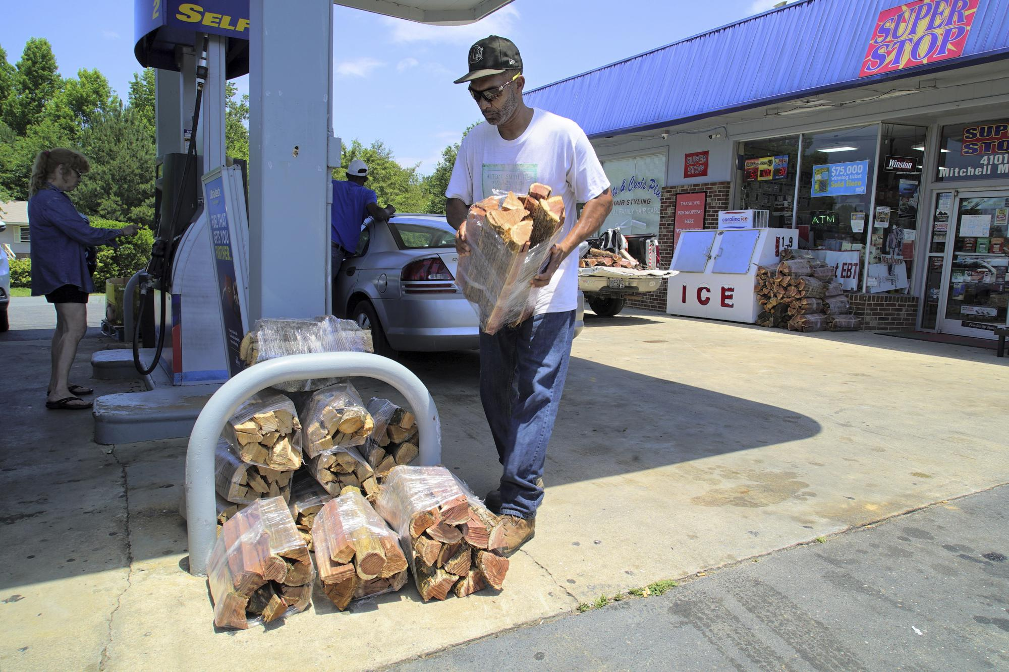 Alton Lucas delivers wrapped firewood to a convenience store near his home outside of Raleigh, N.C., on Friday, June 18, 2021. It's one of the many jobs he performs as part of his Sunflower Landscaping, a business he founded through the program Inmates to Entrepreneurs, a national nonprofit assisting people with criminal backgrounds by providing practical entrepreneurship education. (AP Photo/Allen G. Breed)