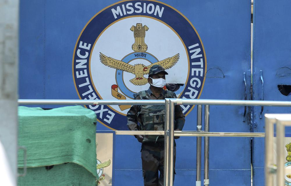 An Indian army soldier stands guard at the main gate of Jammu air force station after two suspected blasts were reported early morning in Jammu, India, Sunday, June 27, 2021. Indian officials said Sunday they suspected explosives-laden drones were used to attack the air base in the disputed region of Kashmir, calling it the first such incident of its kind in India.