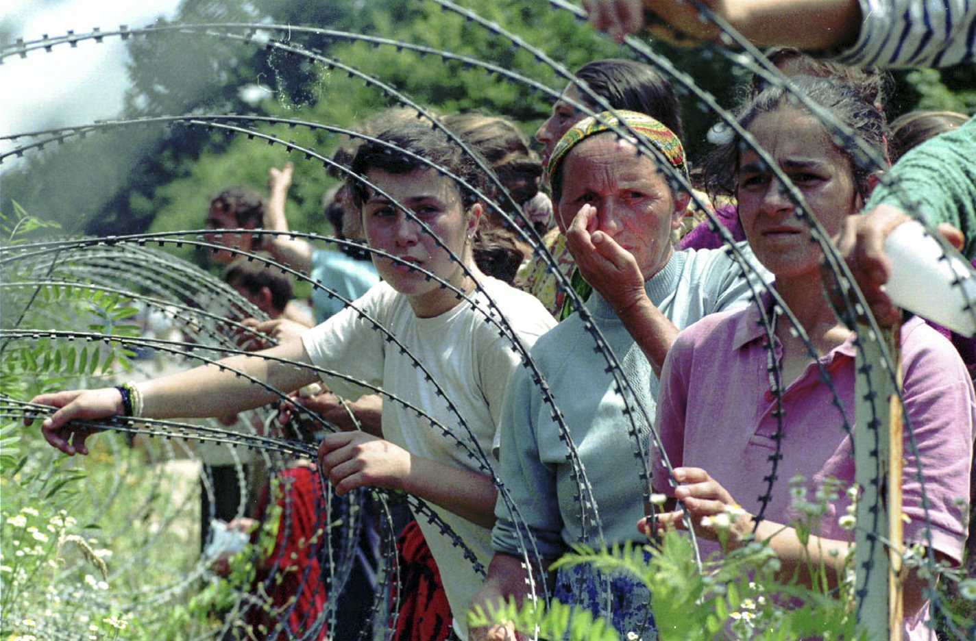 FILE- In this Thursday, July 13, 1995, file picture, refugees from Srebrenica look through the razor-wire at a UN base, outside Tuzla.  Survivors of the genocide in the eastern Bosnian town of Srebrenica, mainly women, will on Saturday July 11, 2020, commemorate the 25th anniversary of the slaughter of their fathers and brothers, husbands and sons.  At least 8,000 mostly Muslim men and boys were chased through woods in and around Srebrenica by Serb troops in what is considered the worst carnage of civilians in Europe since World War II. The slaughter was also the only atrocity of the brutal war that has been confirmed an act of genocide.(AP Photo/Darko Bandic, File)