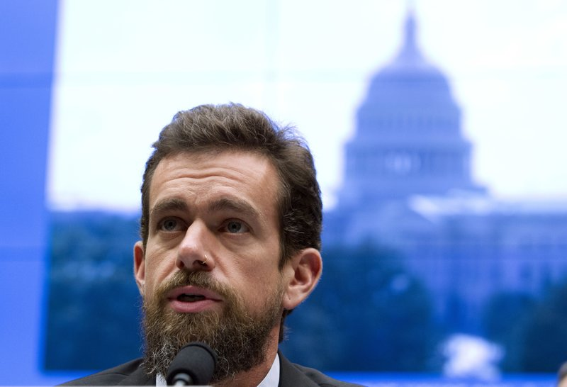 Twitter CEO speaking into a microphone with an image of the White House behind him