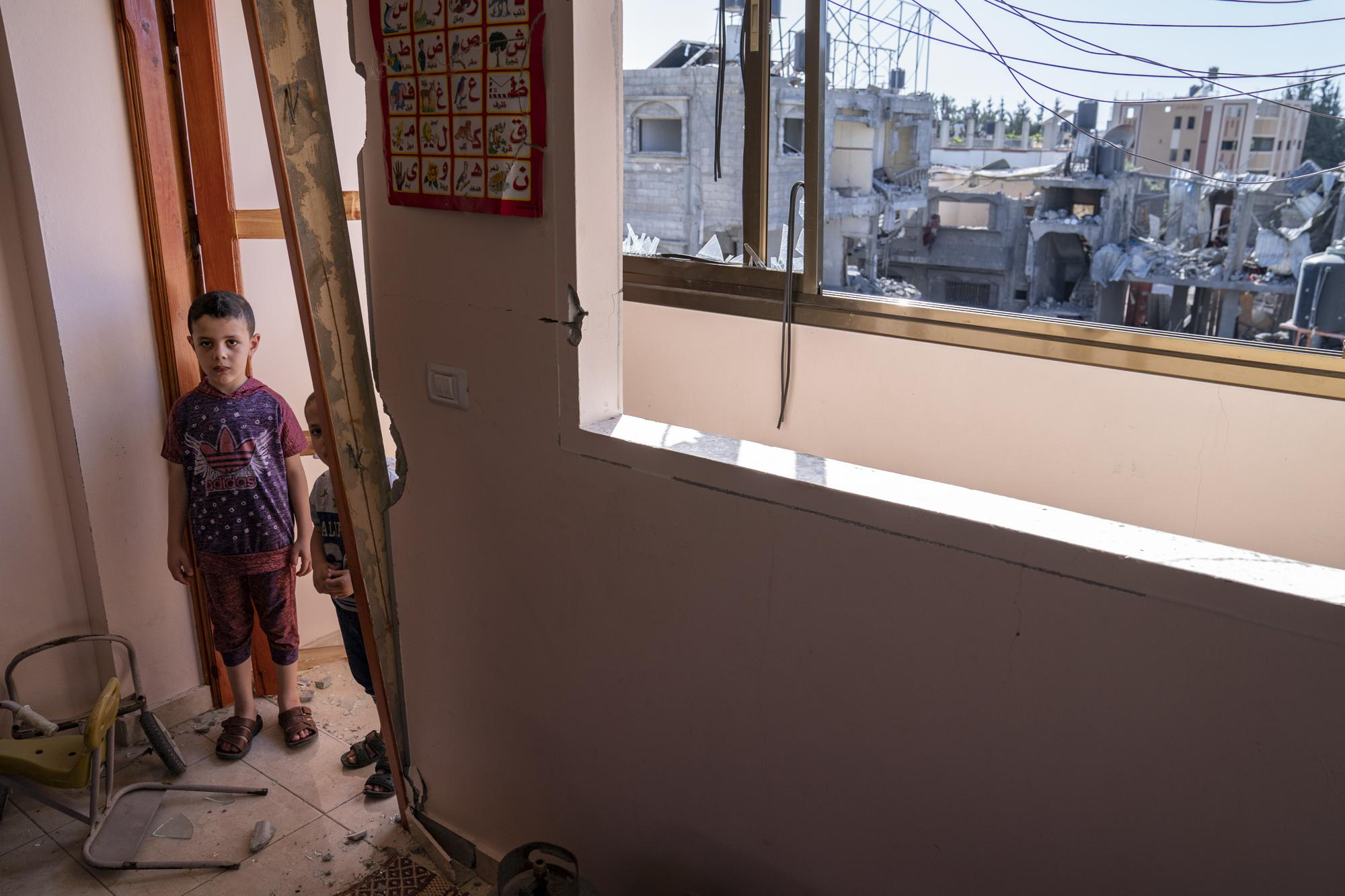 Awny Abed, 6, left, and his brother Salem, 5, stand for a portrait in their bedroom that was damaged when an airstrike destroyed the neighboring building prior to a cease-fire that halted an 11-day war between Gaza's Hamas rulers and Israel, Thursday, May 27, 2021, in Maghazi, Gaza Strip. (AP Photo/John Minchillo)
