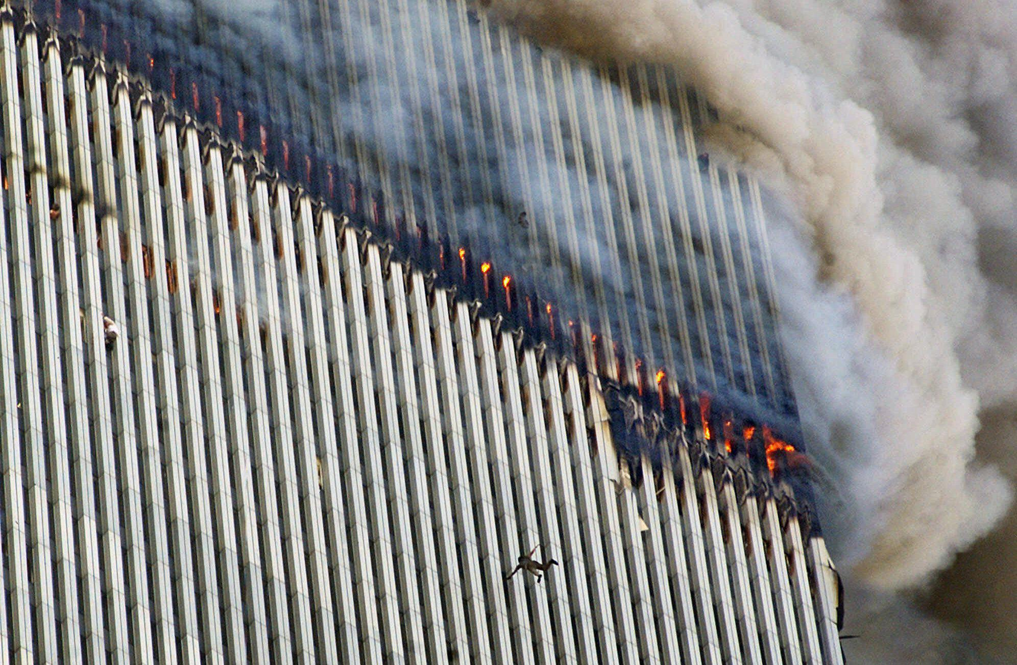 A person falls from the north tower of New York's World Trade Center as another clings to the outside, left, while smoke and fire billow from the building, Tuesday Sept. 11, 2001. (AP Photo/Richard Drew)