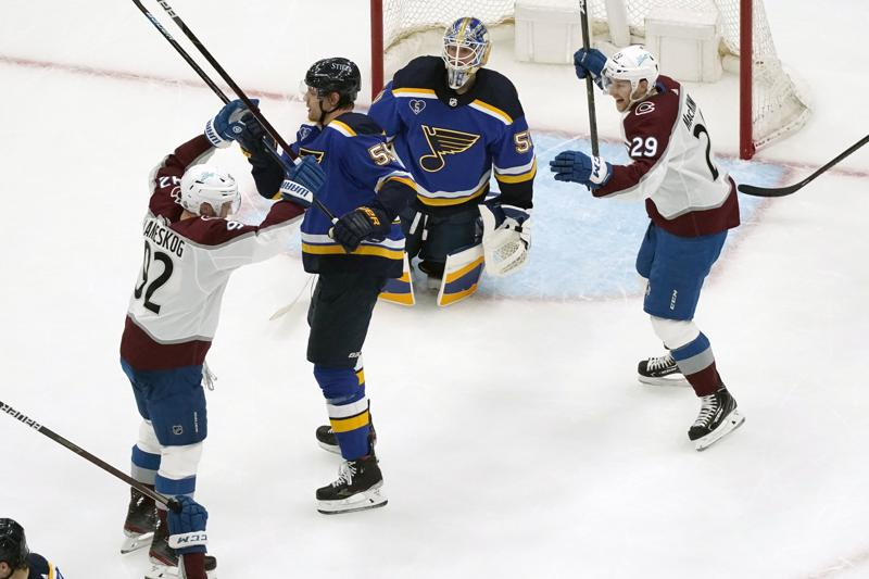 Colorado Avalanche's Gabriel Landeskog, left, is congratulated by teammate Nathan MacKinnon (29) after scoring past St. Louis Blues goaltender Jordan Binnington (50) and Colton Parayko (55) during the second period in Game 4 of an NHL hockey Stanley Cup first-round playoff series Sunday, May 23, 2021, in St. Louis. (AP Photo/Jeff Roberson)