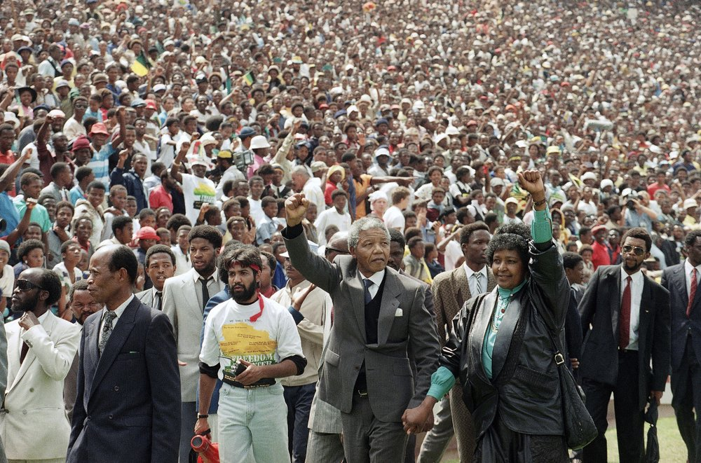 FILE - In this Feb.  13, 1990 file photo, Nelson Mandela and his wife, Winnie Madikizela-Mandela, gesture as they arrive at Soccer City Stadium in Soweto, South Africa two days after being released after serving 27 years in prison.  Mandela's release set off joyous celebrations and violent clashes as supporters welcomed Mandela back from years in jail.  (AP Photo/Udo Weitz, File)