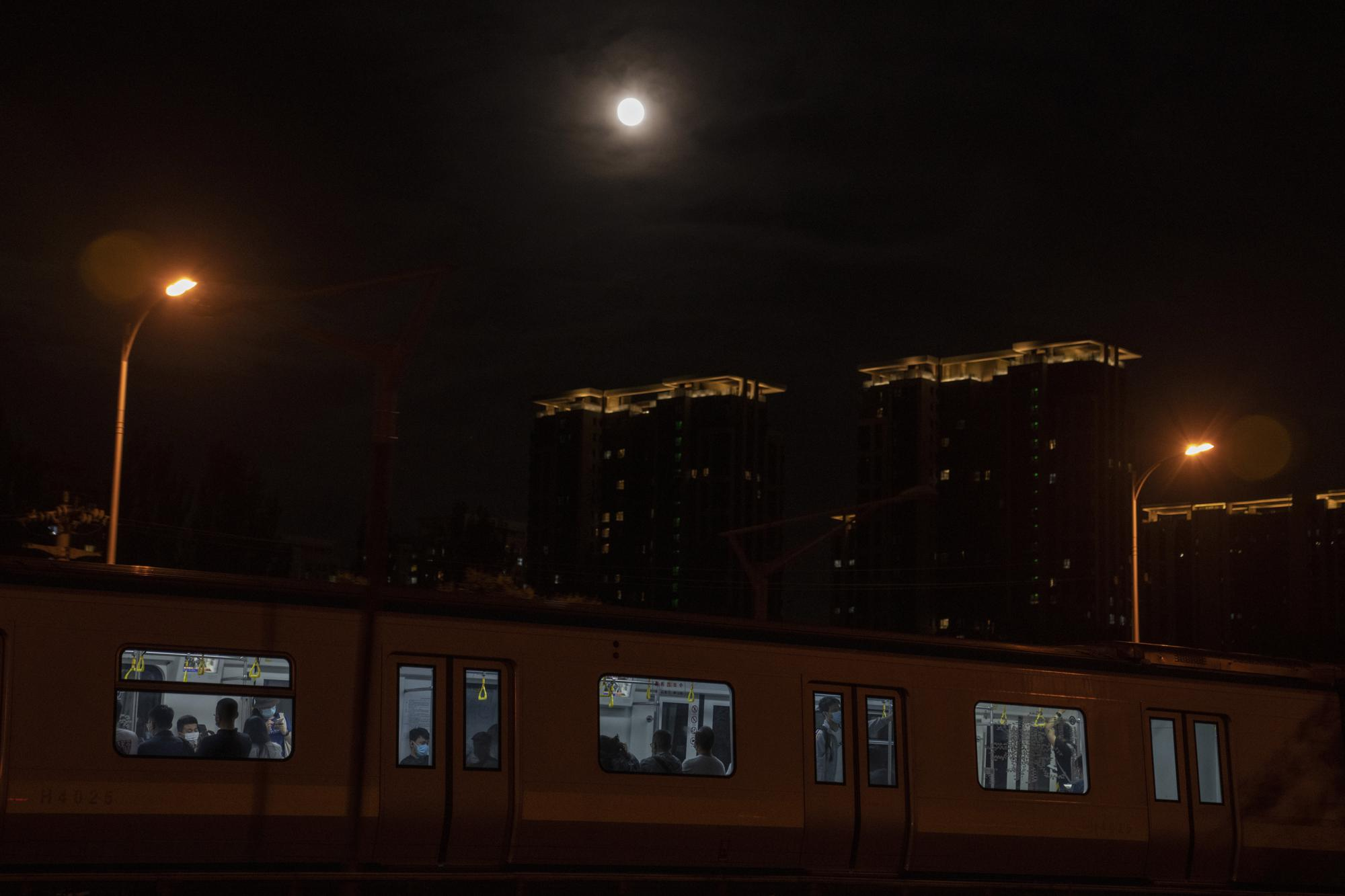 A supermoon rises over a train carrying passengers in Beijing on Wednesday, May 26, 2021. (AP Photo/Ng Han Guan)