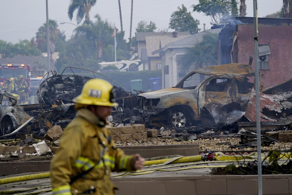 Fire crews work the scene of a small plane crash, Monday, Oct. 11, 2021, in Santee, Calif. At least two people were killed and two others were injured when the plane crashed into a suburban Southern California neighborhood, setting two homes ablaze, authorities said. (AP Photo/Gregory Bull)