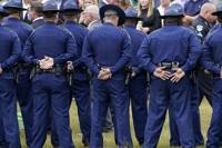 FILE - In this Friday, Sept. 25, 2020 file photo, troopers gather during the burial services for Louisiana State Police Master Trooper Chris Hollingsworth in West Monroe, La. Hollingsworth died in a single-car crash hours after he learned he had been fired for his role in the in-custody death of Ronald Greene. As the Louisiana State Police reel from a sprawling federal investigation into the deadly 2019 arrest of Greene, a Black motorist, and other beating cases, dozens of current and former troopers tell The Associated Press of an entrenched culture at the agency of impunity, nepotism and in some cases outright racism. (AP Photo/Rogelio V. Solis)
