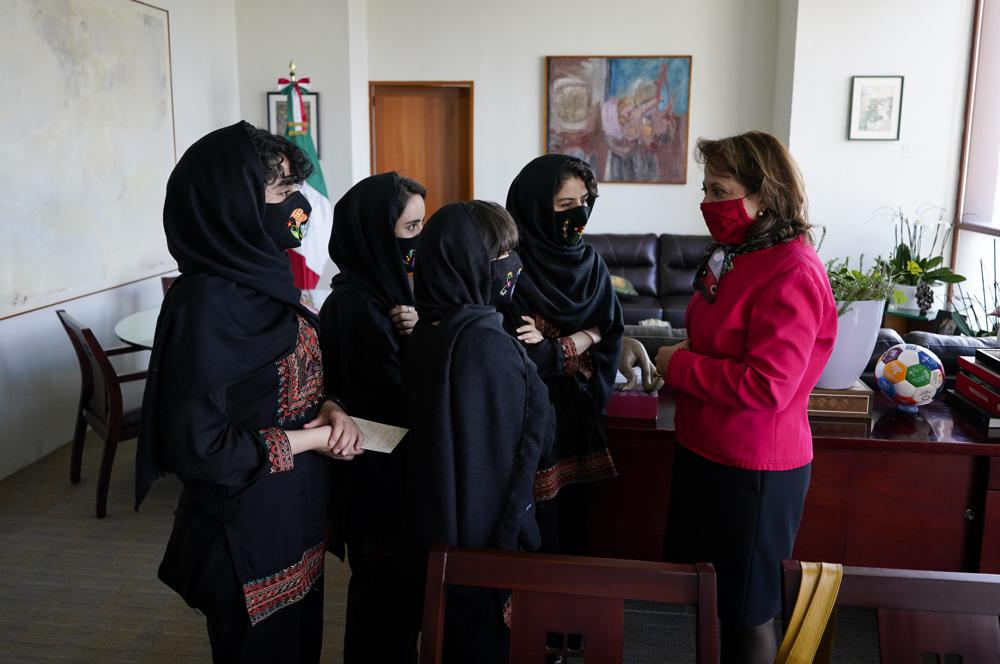 Martha Delgado, Undersecretary for Multilateral Affairs and Human Rights at the Ministry of Foreign Relations of Mexico, talks with members of the Afghan all-girls robotics team, after aninterview in Mexico City, Wednesday, Aug. 25, 2021. After international efforts and coordination from a diverse group of volunteers to evacuate the team, the girls are begging the international community to help get their families to safety amid evacuations for people fleeing the Taliban takeover as the U.S. pulls out. (AP Photo/Eduardo Verdugo)