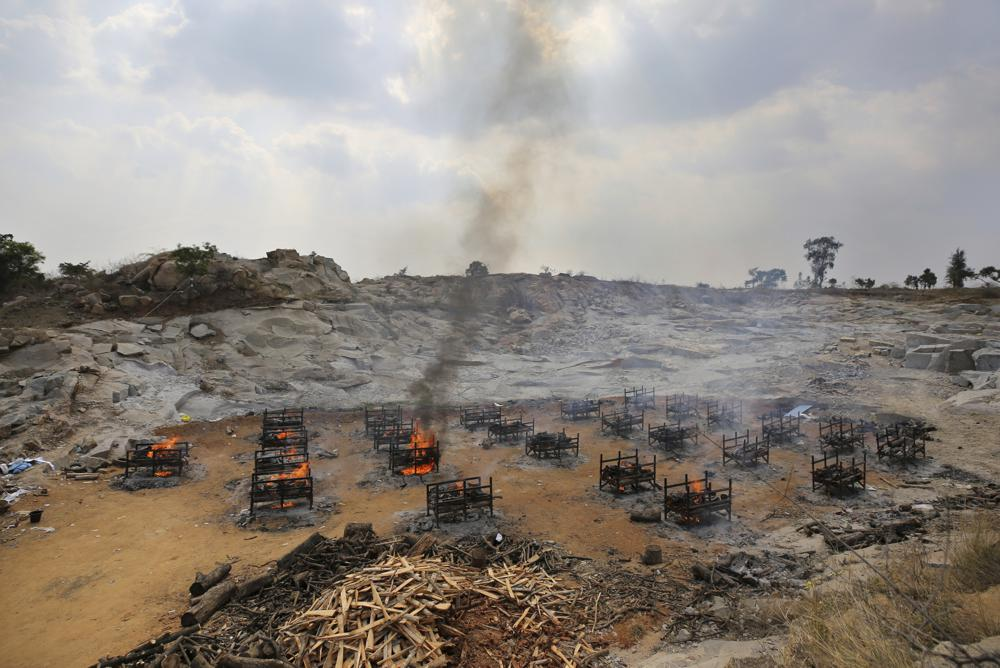FILE - In this May 5, 2021, file photo, funeral pyres of twenty-five COVID-19 victims burn at an open crematorium set up at a granite quarry on the outskirts of Bengaluru, India. India's excess deaths during the pandemic could be a staggering 10 times the official COVID-19 toll, likely making it modern India's worst human tragedy, according to the most comprehensive research yet on the ravages of the virus in the south Asian country. (AP Photo/Aijaz Rahi, File)