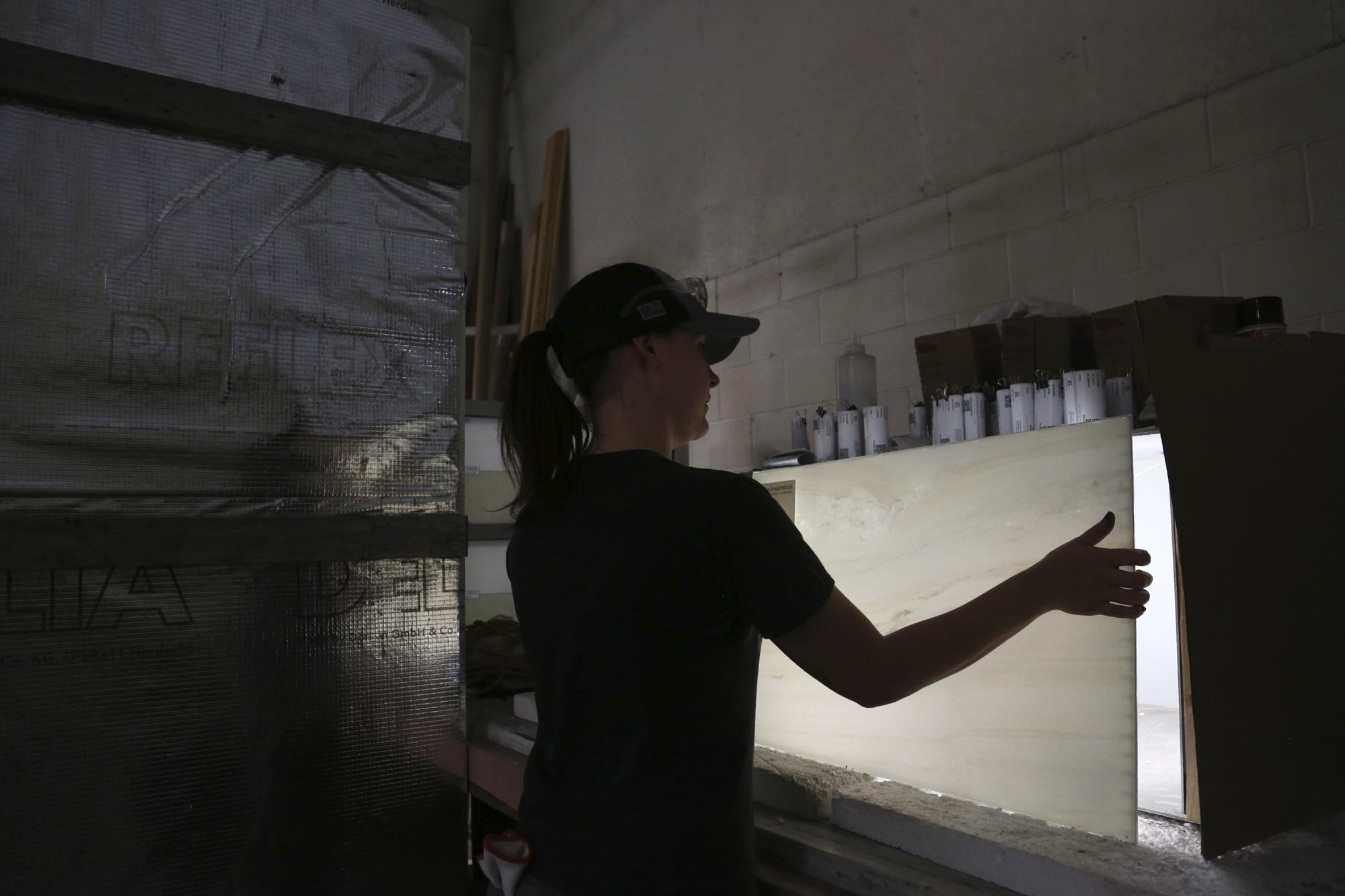Nicole Taylor, an apprentice with MG McGrath Inc., illuminates a thin panel of marble while testing its quality on Thursday, Aug. 5, 2021, in Maplewood, Minn. The marble was mined from the same Pentelic vein in Greece that sourced the Parthenon, the ancient temple in Athens, and will be installed on the outer walls of the new St. Nicholas Greek Orthodox Church and National Shrine at ground zero in New York. The original St. Nicholas, which sat just below the World Trade Center's south tower, was the only house of worship destroyed in the Sept. 11, 2001 attacks. (AP Photo/Jessie Wardarski)