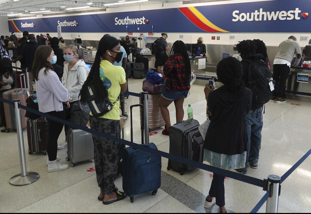 Passengers wait in line at the Southwest Airlines ticket counter at Fort Lauderdale Hollywood International Airport, Monday, Oct. 11, 2021. The Dallas-based airline canceled hundreds of flights Monday following a weekend of major service disruptions. (Joe Cavaretta/South Florida Sun-Sentinel via AP)
