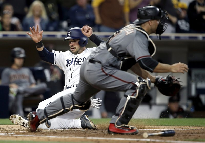 San Diego Padres' Austin Hedges, left, scores as the throw to Arizona Diamondbacks catcher Chris Iannetta is late, on a two-run double by Erick Aybar during the fifth inning of a baseball game in San Diego, Thursday, April 20, 2017. (AP Photo/Alex Gallardo)