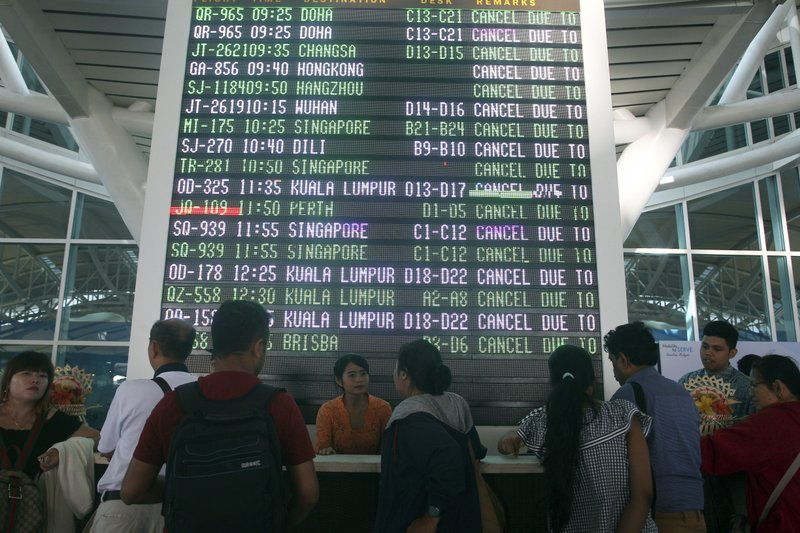 A flight information board shows cancelled flights at Ngurah Rai International Airport in Bali, Indonesia Friday, June 29, 2018. The Indonesian tourist island of Bali closed its international airport Friday, stranding thousands of travelers, as the Mount Agung volcano gushed a 2,500-meter (8,200-feet) column of ash and smoke.