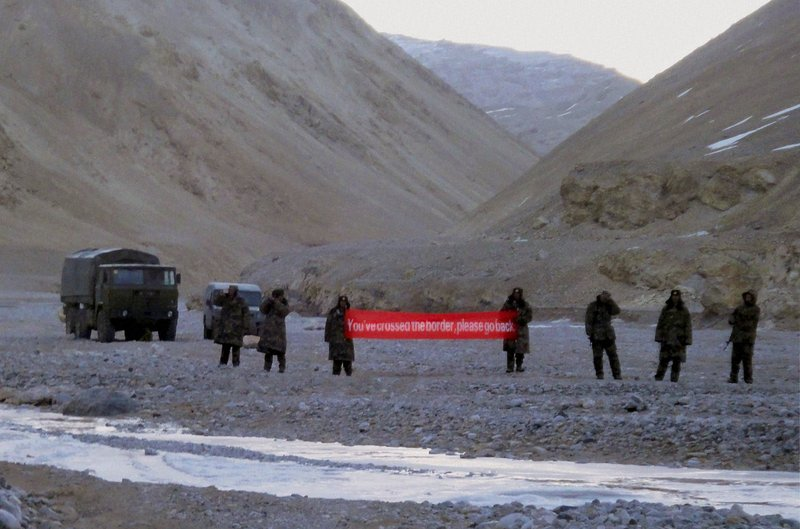 "In this Sunday, May 5, 2013, file photo, Chinese troops hold a banner which reads ""You've crossed the border, please go back"" in Ladakh, India. India says it is ready to hold talks with China with both sides pulling back their forces to end a standoff along a disputed territory high in the Himalayan mountains."