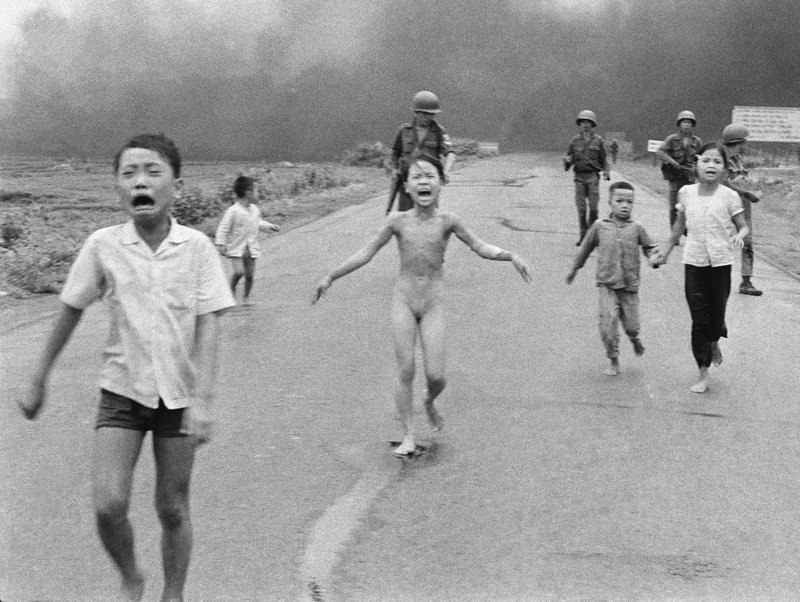 """In this June 8, 1972 file photo taken by Huynh Cong """"Nick' Ut, South Vietnamese forces follow terrified children, including 9-year-old Kim Phuc, center, as they run down Route 1 near Trang Bang after an aerial napalm attack on suspected Viet Cong hiding places. After making the photo, he set aside his camera, gave the badly burned girl water, poured more on her wounds, then loaded her and others into his AP van to take them to a hospital. When doctors refused to admit her, saying she was too badly burned to be saved, he angrily flashed his press pass. The next day, he told them, pictures of her would be displayed all over the world, along with an explanation of how the hospital refused to help. (AP Photo/Nick Ut, File)"""