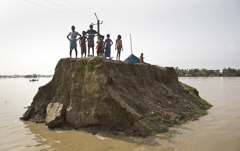 In this Aug. 15, 2017, file photo, flood-affected villagers wait for relief material on what's left of a road washed away by floodwaters in Morigaon district, east of Gauhati, northeastern state of Assam. Deadly landslides and flooding are common across South Asia during the summer monsoon season that stretches from June to September.